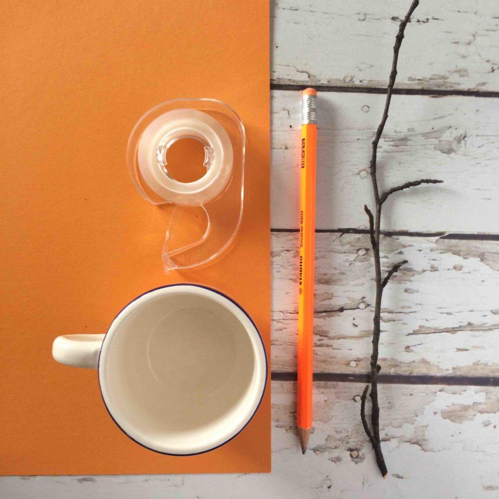 cosa serve per fare le zucche di carta: cartoncino arancione, forbici, un rametto nostro biadesivo